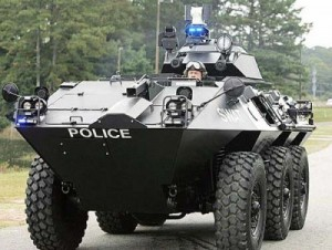 Photo of a small town police SWAT team member in an armored military vehicle. Police departments are becoming militarized throughout the country. www.independentsentinel.com